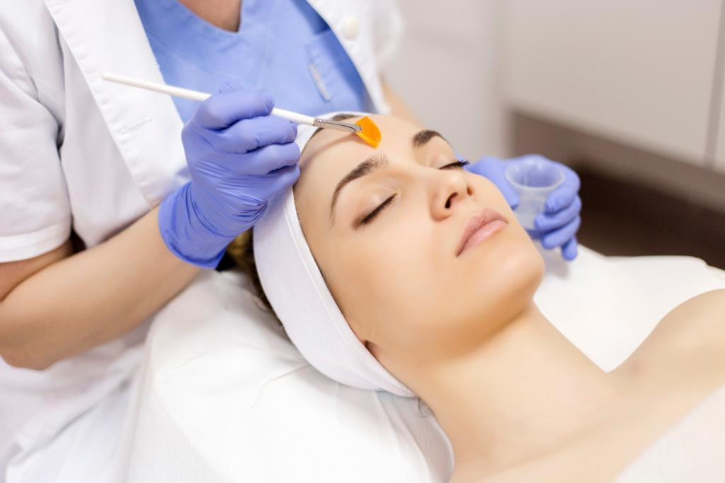 Peeling kwasem migdałowym wykonywany w salonie kosmetycznym. Widok twarzy pacjentki i rąk kosmetyczki, które trzymają kwas i pędzelek.